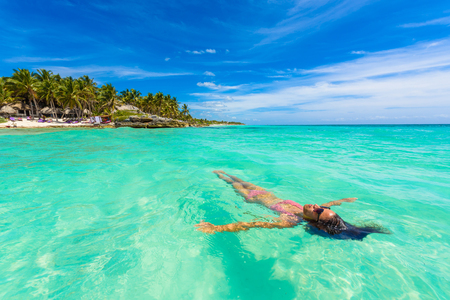 Photo pour Attractive young woman relaxing in turquoise waters of Caribbean Sea in front of paradise beach in Tulum, close to Cancun, Riviera Maya, Mexico - image libre de droit