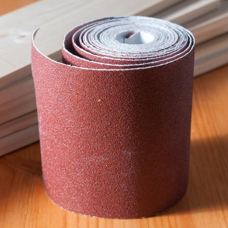 Foto de Sandpaper rolls on a wood table - Imagen libre de derechos