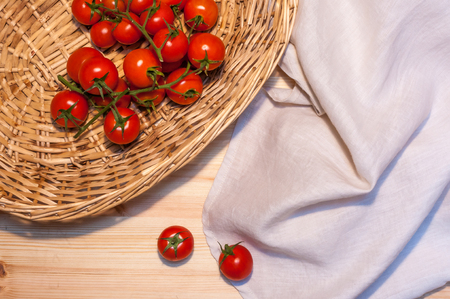 Cherry tomatoes in a wicked basket and a linen tablecloth on a wood table for background or banner. Horizontal composition.