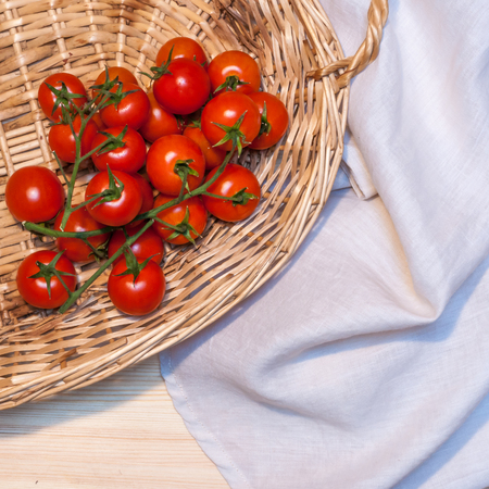 Cherry tomatoes in a wicked basket and a linen tablecloth on a wood table for background or banner. Square composition.