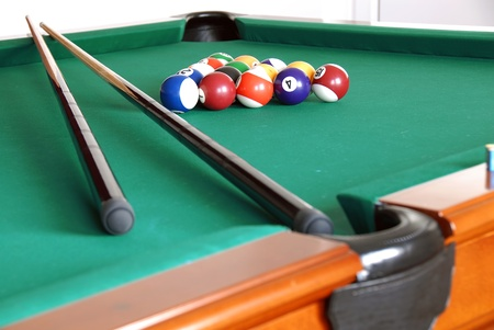 billiards green table with balls and two black cues