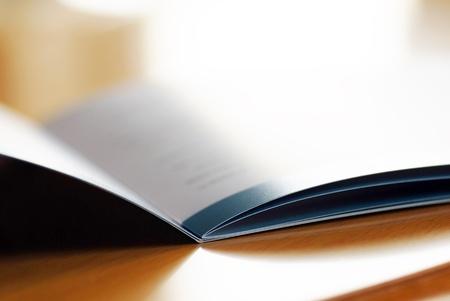 Photo pour opened brochure closeup on brown desk macro - image libre de droit