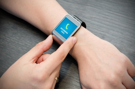 Photo pour Incoming call notification on smart watch connected to smart phone - image libre de droit