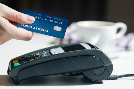 Photo for Woman hand using payment terminal in restaurant - Royalty Free Image