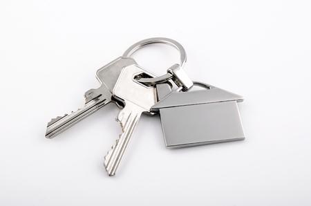 Foto de Keys and house chrome pendant with home shape isolated on white background - Imagen libre de derechos