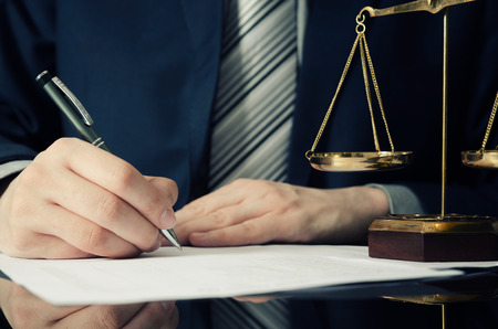 Foto de Lawyer working with agreement in office. man signing hand writing pen attorney concept - Imagen libre de derechos