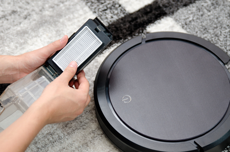 Photo pour Robotic vacuum cleaner. Hepa filter cleaning. Maintenance concept. - image libre de droit