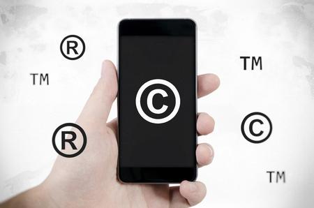 Foto de Copyright, trademark symbols flying around smartphone. Security and piracy composition. Dirty noise style - Imagen libre de derechos