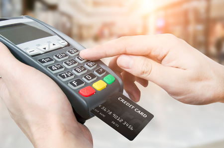 Photo for Hand with credit card swipe through terminal for sale in supermarket - Royalty Free Image