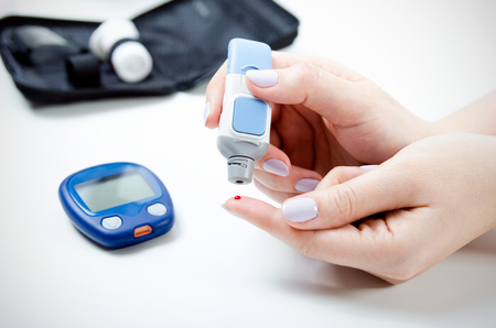 Foto de Diabetes doing blood glucose measurement. Woman using lancet and glucometer. - Imagen libre de derechos