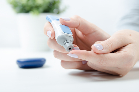 Photo pour Diabetes doing blood glucose measurement. Woman using lancet and glucometer. - image libre de droit