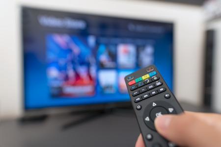 Foto de Multimedia streaming concept. Hand holding remote control. Video on demand - Imagen libre de derechos
