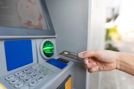 Photo pour Man hand puts credit card into ATM. Money is withdrawn from an ATM. - image libre de droit