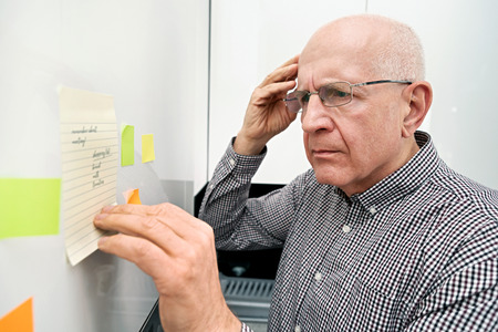 Foto de Elderly man looking at notes. Forgetful senior with dementia, memory problem, health concept - Imagen libre de derechos