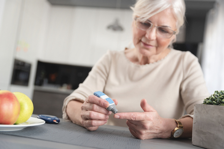 Foto per Senior woman checking her blood glucose level. Health care diabetes concept - Immagine Royalty Free