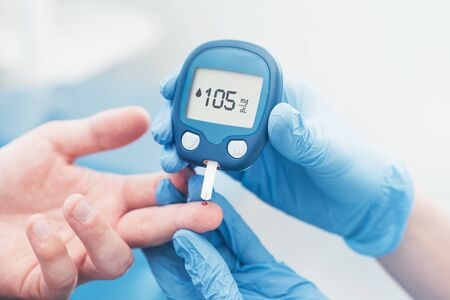 Foto de Doctor checking blood sugar level with glucometer. Treatment of diabetes concept. - Imagen libre de derechos