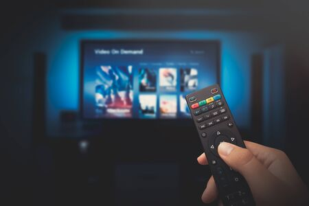 Photo pour VOD service screen. Man watching TV with remote control in hand. - image libre de droit