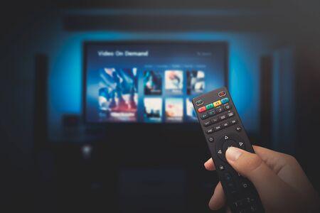 Foto de VOD service screen. Man watching TV with remote control in hand. - Imagen libre de derechos