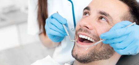 Photo pour Young man at the dentist. Dental care, taking care of teeth. Picture with copy space for background. - image libre de droit