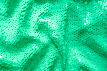 Photo for Background sequin. Holiday abstract glitter background with blinking lights. Fabric sequins in green color. Fashion fabric glitter, sequins. Wallpaper. - Royalty Free Image
