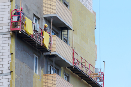 Photo pour Workers in suspended cradle for facing facade of tall building under construction - image libre de droit