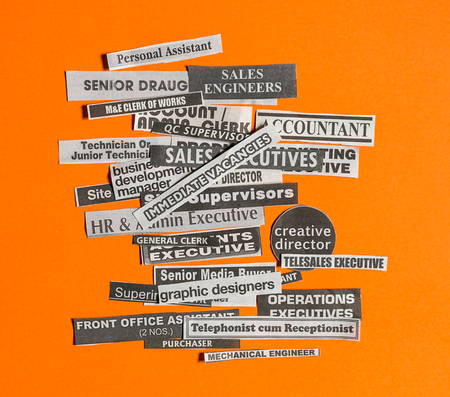 Photo for Jobs or careers concept: multiple job titles or occupations cut off from newspaper with Immediate Vacancies on top of the pile and on orange background - Royalty Free Image