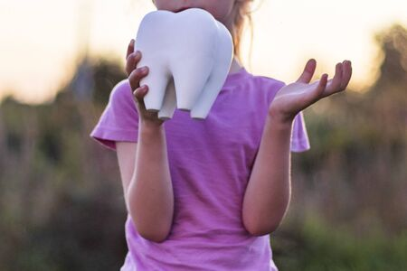 Foto de little girl affliction. holds a large plaster tooth. Shallow depth of field. - Imagen libre de derechos