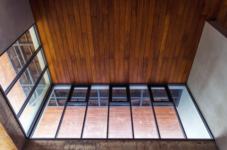 Foto de Aluminum window with wooden ceiling in house under construction - Imagen libre de derechos