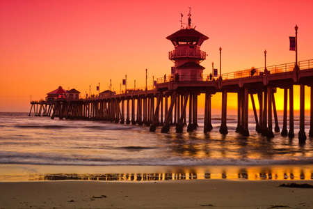 A wide shot of the Huntington Beach Pier during a bright red and orange sunset. mural