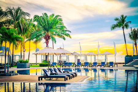 Photo for Umbrella in the luxury hotel pool resort at sunrise times - Vintage filter processing style pictures - Royalty Free Image