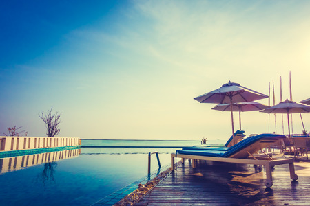 Photo for Beautiful luxury swimming pool in hotel resort with umbrella and chair in sunset times - Vintage Filter and Boost up color processing - Royalty Free Image