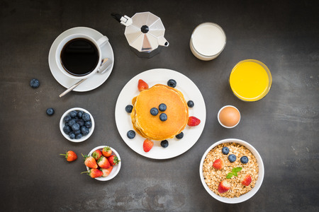 Foto de Healthy Breakfast set with Pancake and Granola with blueberry and strawberry and black coffee , Milk and Orange juice on table - Imagen libre de derechos
