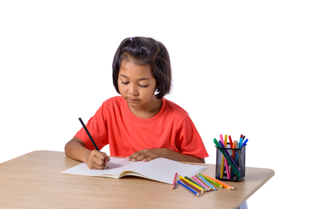 Foto de Cute cheerful child drawing using color pencil while sitting at table isolated on white background with clipping path. Education study home school - Imagen libre de derechos