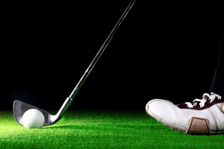 man ready to hit golf ball with golf iron on black background
