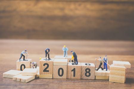 Foto de Miniature worker team building wooden block number 2018 on wooden background - Imagen libre de derechos