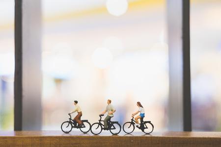 Photo pour Miniature people : Travellers with bicycle on wood bridge - image libre de droit