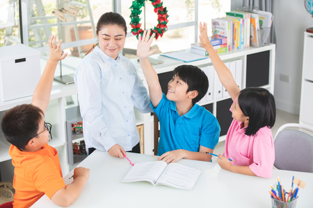 Foto de Young asian teacher ask question young kids in classroom . - Imagen libre de derechos