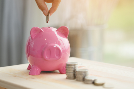 Photo pour Little hand saving money in pink piggy bank - image libre de droit