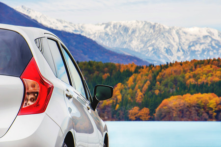 Photo pour Road Trip Concept, Car Driving Travel in Autumn Season, Lake, beautiful Foliage and Mountains covered by Snow as background - image libre de droit
