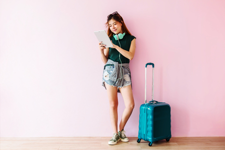 Photo pour Happy Young Traveler Woman with Suitcase and Music Headphone using Tablet and Smiling, Full Length,Technology on Traveling, Lifestyle of Modern People - image libre de droit