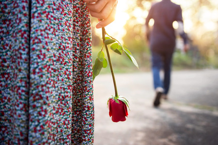 Foto de Sadness Love in Ending of Relationship Concept, Broken Heart Woman Standing with a Red Rose on Hand, Blurred Man in Back Side Walking away as background  - Imagen libre de derechos