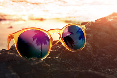 Photo for Closeup of Sunglasses with Reflection of Coconut Palm Tree on Island, Sunset as background, Warm and Vintage tone, Travel the Beach in Summer or Protect Eyes from Sunlight Concept - Royalty Free Image