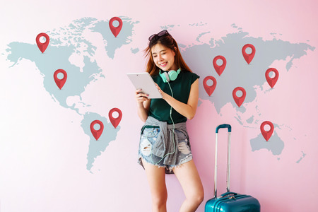 Foto per Happy Young Traveler Woman standing with Suitcase and using Tablet to Finding her Destination for Next Trip. Technology on Traveling Concept. World Map with Mark Icon on the Wall - Immagine Royalty Free