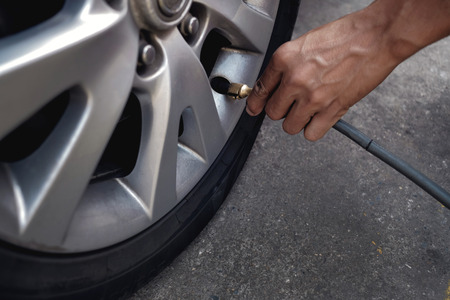 Photo pour Man filling Air into the Tire. Car Driver Checking Air Pressure and Maintenance his Car by himself before Traveling - image libre de droit