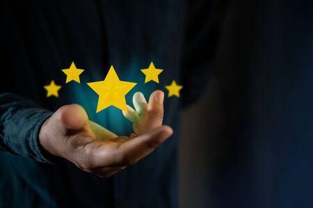 Foto de Customer Experiences Concept. Person Giving Positive Review for Client's Satisfaction Surveys. Five Stars Rating floating on Hand. Dark Tone - Imagen libre de derechos