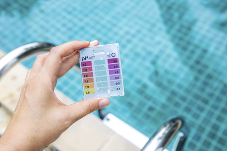 Foto de Girl hand holding mini water testing test kit over blurred swimming pool background, outdoor day light - Imagen libre de derechos