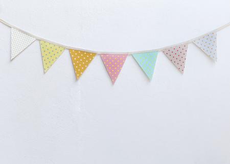 Foto de Design vintage fabric party flag over white cement wall texture background, outdoor day light - Imagen libre de derechos