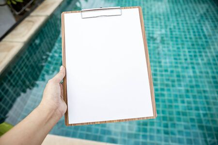 Photo pour Blank white paper on wooden clipboard over blurred swimming pool background, pool check list - image libre de droit