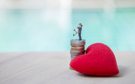Photo pour Happy couple standing on coin stack with red heart over blurred background - image libre de droit