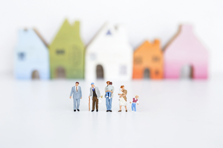 Photo for Miniature group of different kind of people over blurred house on white background - Royalty Free Image